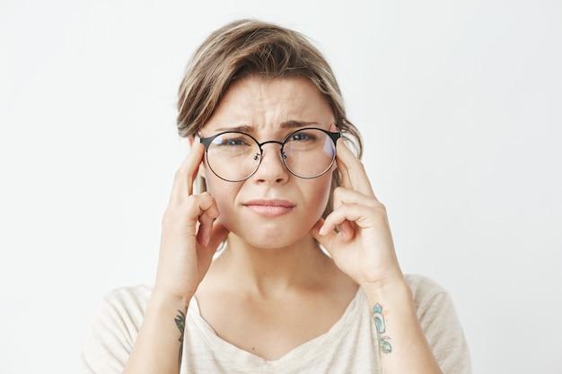 Chica guapa joven en gafas pensando frunciendo el ceño con los dedos en las sienes.