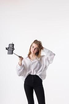 Chica guapa joven haciendo autorretrato con teléfono inteligente conectado a selfie stick