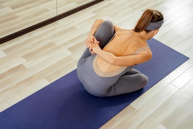 Chica guapa joven haciendo pose de yoga, mujer practicando yoga interior