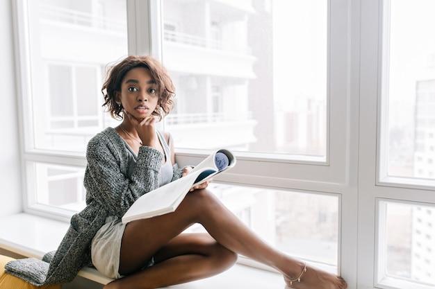 Chica guapa joven con mirada sorprendida sentada en el alféizar de la ventana, gran ventana blanca, leyendo una revista, libro. lleva chaqueta de punto gris, camiseta, pantalón corto, brazalete de oro en la pierna.