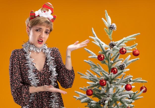 Chica guapa joven molesta con diadema de santa claus y guirnalda de oropel alrededor del cuello de pie cerca del árbol de navidad decorado apuntando hacia él mirando a cámara aislada sobre fondo naranja