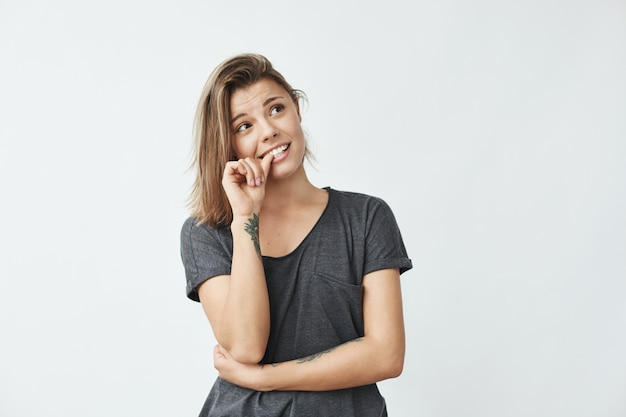 Chica guapa joven nerviosa mirando en las uñas mordidas.