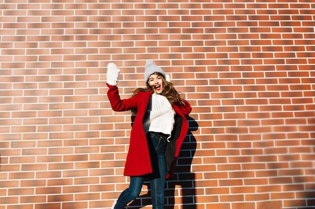 Chica guapa joven con pelo largo en abrigo rojo, sombrero, guantes divirtiéndose en la pared exterior.