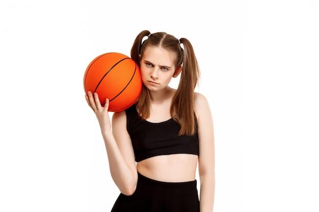 Chica guapa joven posando con baloncesto, aislado en la pared blanca