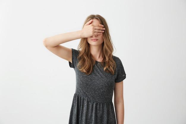Chica guapa joven que cubre los ojos cerrados detrás de la mano.