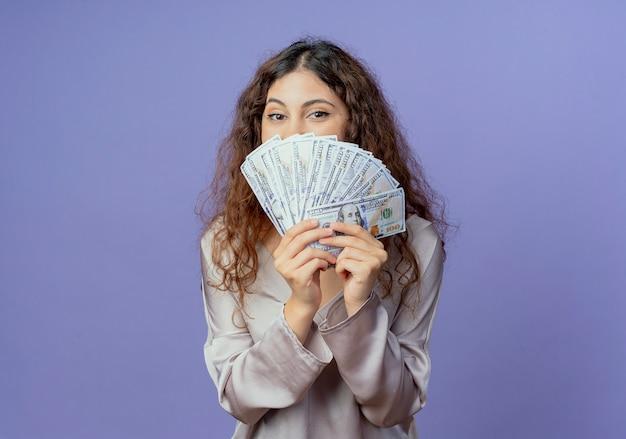 Chica guapa joven rostro cubierto con dinero aislado en la pared azul
