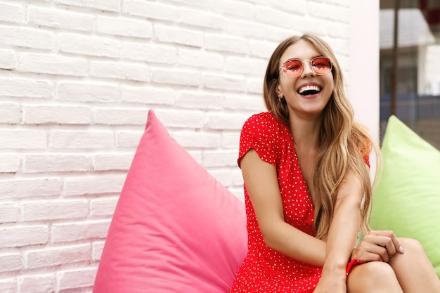 Chica guapa joven sentada en un café al aire libre en un puf rosa y riendo
