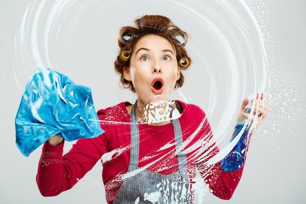 Chica guapa joven sorprendida lava ventanas con una toalla azul