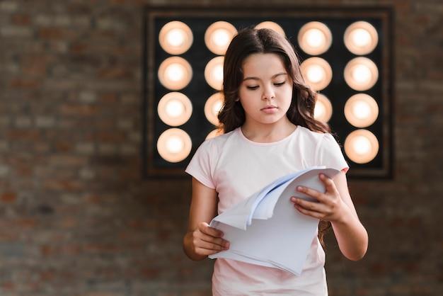 Chica guapa leyendo guiones de pie contra la pared con luz de escenario