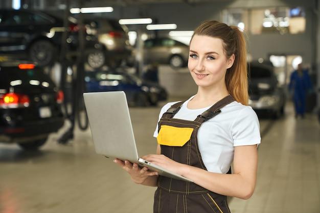 Chica guapa, mecánico posando con notebook en autoservicio.