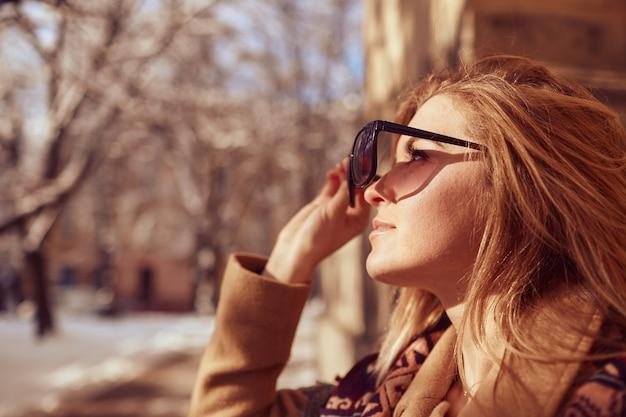 Chica guapa está mirando al sol a través de gafas de sol