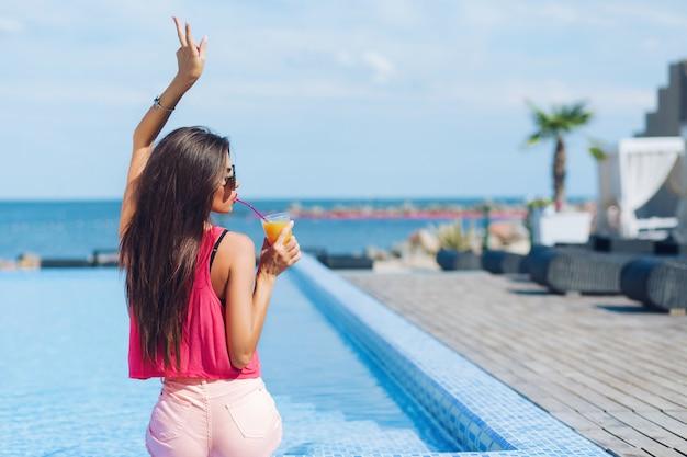 Chica guapa morena con pelo largo está sentada junto a la piscina. ella sostiene la mano arriba y bebe con una pajita. vista desde atrás.