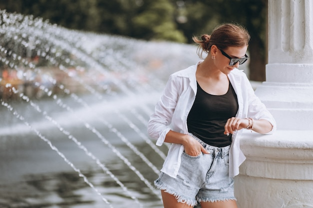 Chica guapa en el parque junto a las fuentes