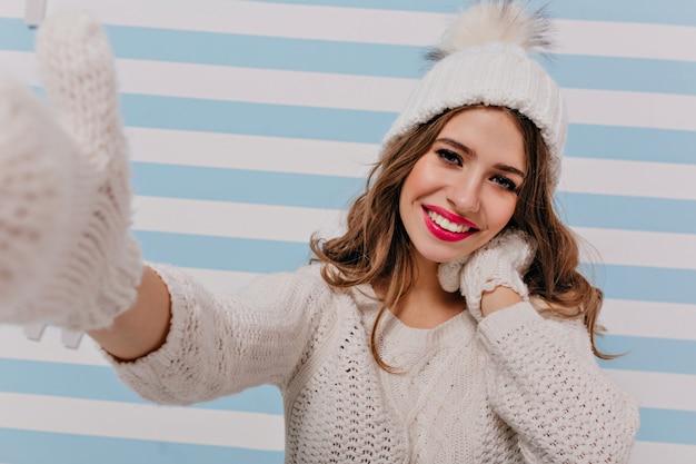 Chica guapa con pelo largo hace felizmente selfie. modelo europeo en poses divertidas de traje de punto de invierno