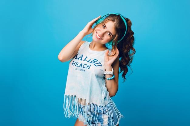 Chica guapa con pelo largo y rizado en cola sobre fondo azul en estudio. viste camiseta blanca, pantalones cortos y escucha música con auriculares azules.