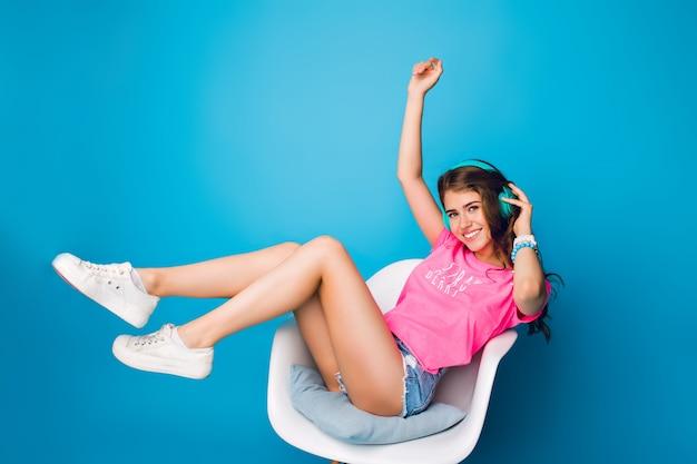 Chica guapa con pelo largo y rizado escuchando música en silla sobre fondo azul en estudio. lleva pantalones cortos, camiseta rosa, zapatillas blancas. ella sostiene las piernas arriba y sonríe a la cámara.