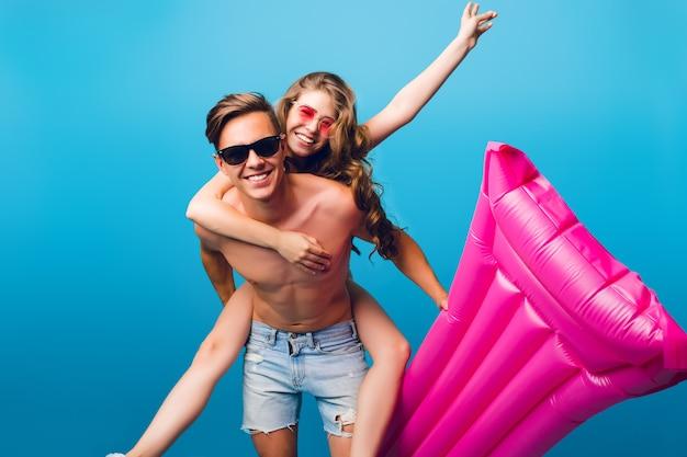 Chica guapa con pelo largo y rizado está montando en la espalda de un chico guapo con el torso desnudo sobre fondo azul en estudio. sostiene un colchón rosa y sonríen a la cámara. se divierten juntos.