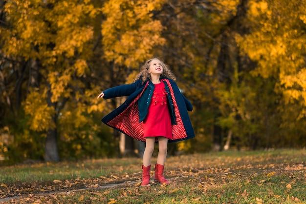 Chica guapa con pelo largo y rizado en el parque otoño