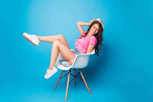 Chica guapa con pelo largo y rizado con sombrero se está enfriando en silla sobre fondo azul en estudio. lleva pantalones cortos, camiseta rosa, zapatillas blancas. ella luce feliz.