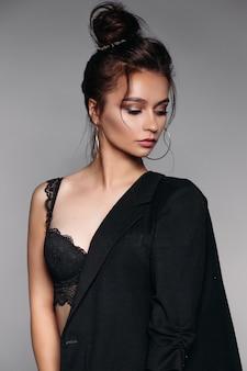 Chica guapa con el pelo recogido con sujetador negro y chaqueta mirando hacia abajo