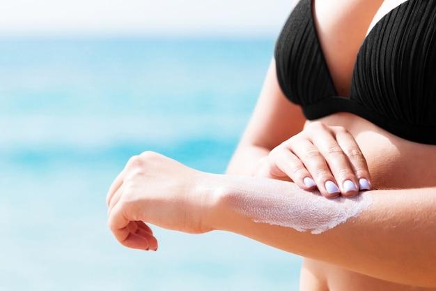 Chica guapa está poniendo crema solar en la mano en la playa.
