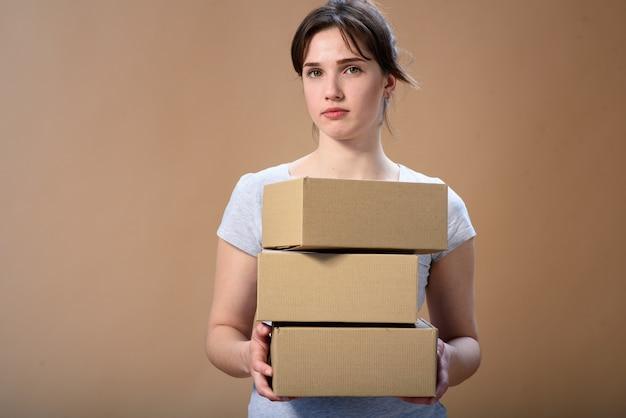 Chica guapa de primer plano con tres cajas de cartón. espacio publicitario gratuito