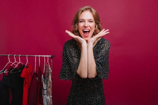 Chica guapa riendo esperando fiesta y eligiendo vestimenta