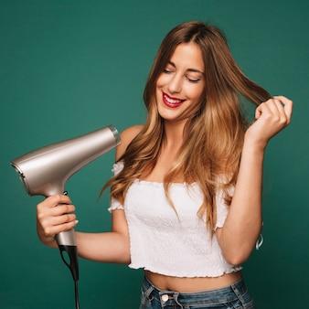 Chica guapa con secador de pelo