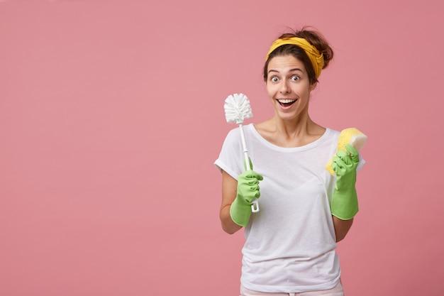 Chica guapa en sentirse sorprendida con noticias inesperadas mientras hace la limpieza general, usa guantes de goma, lava el inodoro, sostiene el cepillo y la esponja, mira, mantiene la boca bien abierta