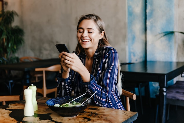 Chica guapa con teléfono durante la cena en la cafetería. retrato de mujer joven feliz comiendo verduras.