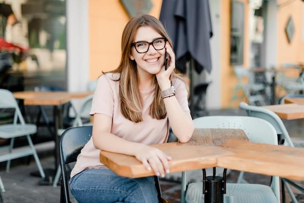 Chica guapa con teléfono sentado en la cafetería