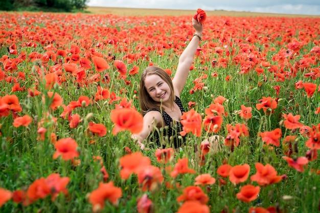 Chica guapa ucraniana disfrutando de flores en el campo. hora de verano