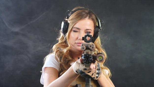Chica guapa en un uniforme de airsoft y auriculares plantea contra un fondo oscuro con humo en el fondo.