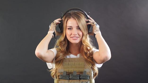Chica guapa en un uniforme de airsoft y auriculares plantea contra un fondo oscuro con humo.