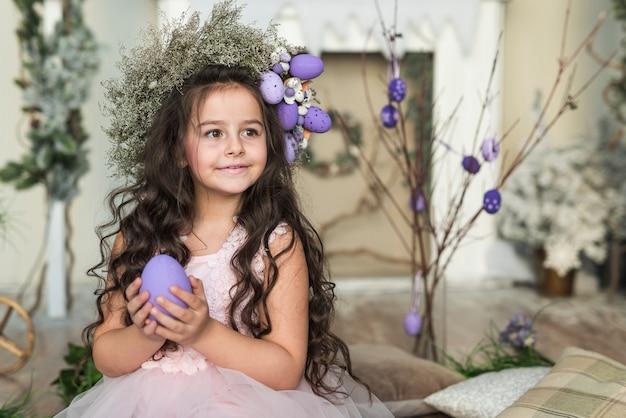 Chica en guirnalda de flores con huevo de pascua