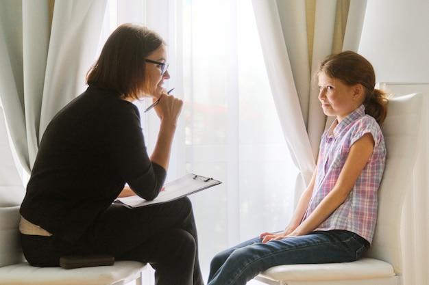 Chica hablando con psicóloga consejera discutiendo los sentimientos del niño