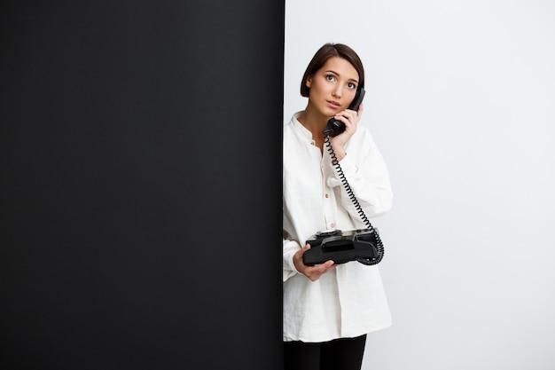 Chica hablando por teléfono antiguo sobre pared blanco y negro