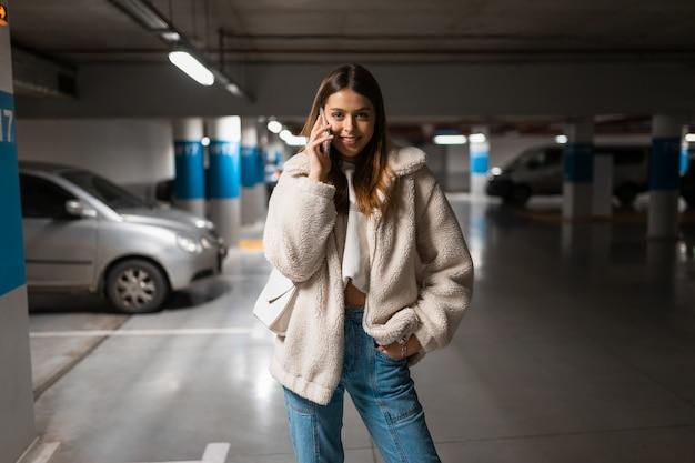 Chica hablando por teléfono en el estacionamiento subterráneo