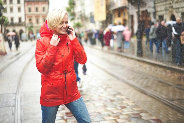 Chica hablando por teléfono bajo la lluvia en la calle. retrato de mujer joven muy sonriente en impermeable rojo brillante. soleado día de lluvia en la ciudad