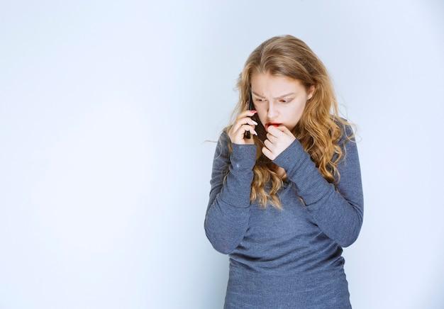 Chica hablando por teléfono y parece aterrorizada.