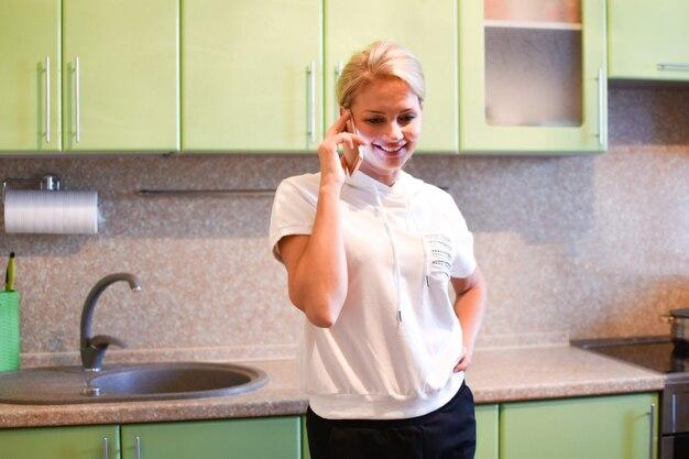 Chica hablando por teléfono por teléfono en la cocina del apartamento