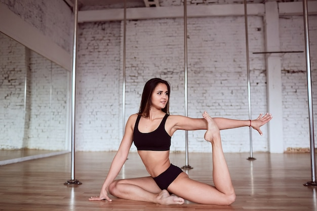 La chica hace estiramientos para las piernas y la espalda antes del entrenamiento de pole dance en el gimnasio