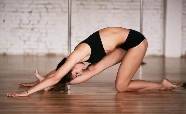 Chica hace estiramientos de su espalda y piernas antes de un entrenamiento en el gimnasio de pole dance