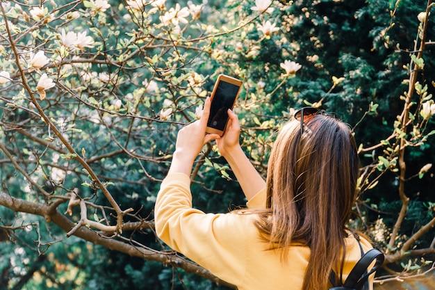 Chica hace foto de flor de magniloa en la cámara del teléfono inteligente. medios de comunicación social