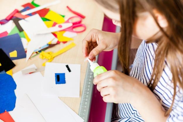 Chica hace manualidades, postales, papel, papel multicolor para la creatividad.