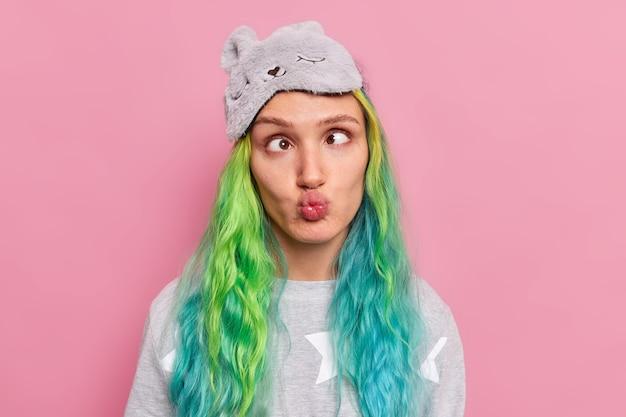 Chica hace ojos locos entrecerra los ojos y hace muecas labios intenta hacer reír a los amigos viste pijama y antifaz tiene el pelo teñido posa en rosa