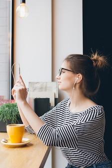 Chica hace selfie en smartphone en cafetería