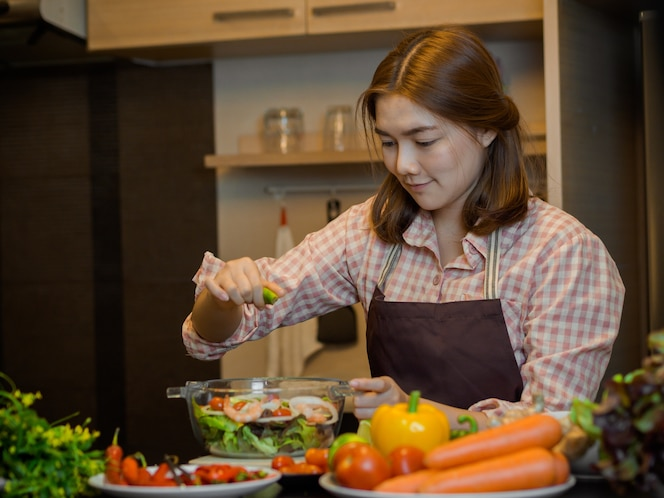 Chica haciendo comida limpia y ensalada en el concepto de cocina