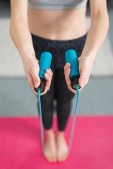 Chica haciendo ejercicio con cuerda de saltar en su casa