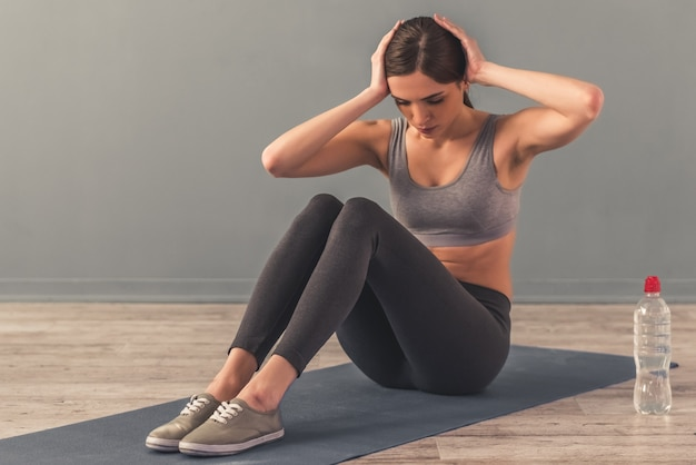 Chica está haciendo ejercicios abdominales en la estera de yoga en casa.